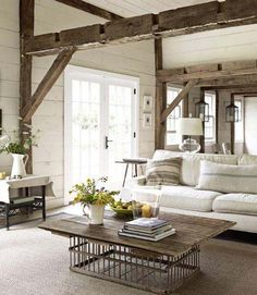 This living room employs clean, modern touches in order to enliven an aged farmhouse interior. A Pottery Barn sofa slipcovered in washable canvas and a bolster pillow that's been hand stitched from a grain sack add new life to impressive exposed wood framing and support beams. Fresh white paneled walls welcome in lots of light. Using an old chicken crate as a base, a homemade coffee table helps retain genuine rustic appeal.