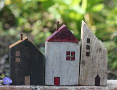 Little wooden houses made from scrap wood board pieces.
