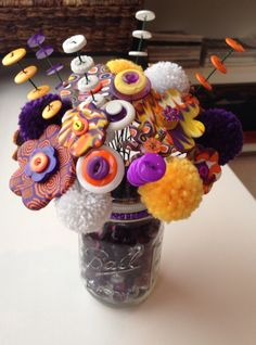 Bouquet of polymer clay flowers, button flowers and stems, Pom poms in a mason jar filled with colored glass beads.