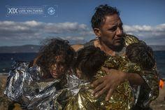 Un padre abraza a sus dos hijas y a su hijo, envueltos en mantas térmicas, justo después de desembarcar en una playa de la isla griega de Lesbos. Al menos 3.770 personas murieron intentando llegar a Europa por el Mediterráneo el pasado año. | Foto: Santi Palacios.