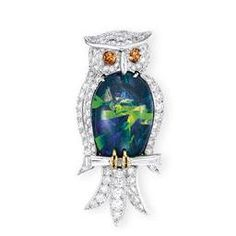 AN OPAL, DIAMOND AND COLOURED DIAMOND 'OWL' BROOCH, BY RUSER  Designed as a brilliant-cut diamond owl, the body set with a black opal measuring approximately 24.0 x 16.0 cm, to the intense brownish orange diamond eyes, perching over a tapered baguette-cut diamond branch, mounted in platinum