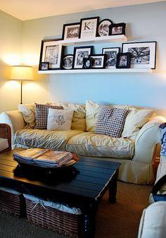 De jolies étagères imposantes chargées de cadres photo au-dessus du sofa.