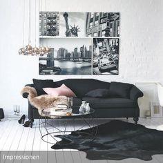 Gegensätze ziehen sich an: Die weißen Dielen bieten die perfekte Bühne für das schwarze Sofa in diesem Wohnzimmer. Passende Deko-Elemente und ein …: