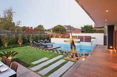 jardin moderne avec gazon, coin repas et parois délimiteuses en verre