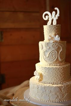 Buttercream piped paisley, adorned with sugar flowers and monogram