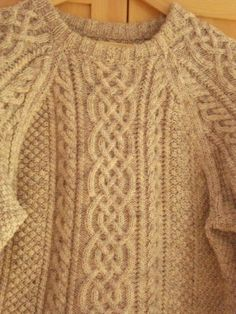 """Handknit Aran Sweater: The origins of the Aran sweater trace back to the Aran Islands off the west coast of Ireland, and the hand-knitting the islands became known for are said to have been introduced as early as the 17th century. Each sweater told of """"clans,"""" almost like a family crest, and these specific patterns were passed down from within each clan from generation to generation, becoming an extremely significant marker of Irish tradition and heritage."""