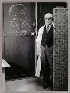 Henri Matisse standing against a screen and drawing with chalk - Brassai