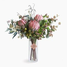 Pink Protea Flower Arrangement: Pink protea, eucalyptus pods, gum nuts, curly twig and mixed foliage. Simple yet beautiful arrangement in a clear glass vase.