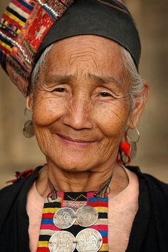 Portrait of an older woman of the Akha Loma tribe with traditional hair dress near Phongsaly, Laos. Photo by Dietmar Temps. Beautiful smile!