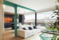 Turquoise accents against black kitchen and neutral-colored living room.