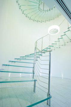 Scala a sbalzo a giorno con gradini in cristallo strutturale extrachiaro e ringhiera a tondini orizzontali in acciaio inox.