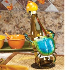 """13"""" Hand Sculpted Wrought Iron Blue Crab Table Top Wine Bottle Holder by CC Home Furnishings. $49.99. Iron Blue Crab Wine Bottle HolderItem #DFA1871The perfect blend of design and function makes this wine holding figure an eye-catching and useful addition to any table.Product Features:The unique blue crab wine bottle holder includes a """"body"""" that supports the bottle by encircling its lower half and a yellow seashell that covers its top connected by a delicate chainH..."""