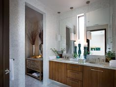 A cinnamon-colored double vanity warms up this contemporary white bathroom while providing lots of storage space. Stunning white mosaic tile walls turn the space into a spa-like atmosphere.