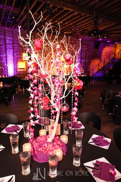 Trees with Orchids and hanging LED globes filled with petals for a dramatic centerpiece arrangement