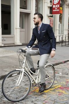 street style: elegant man on bike in  navy jacket and grey pants