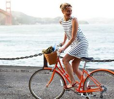 Love everything in this pic...dress, orange bike with basket, and of course, the bridge.