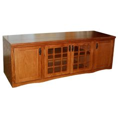 "This 72"" Widescreen TV Stand with Mission Lattice design features bottom wooden doors as well as center glass doors. The center shelf as well the other two on the ends are all adjustable. This tv stand is constructed in the United States using solid oak and oak veneer over plywood on the sides and backs. This unit's welcoming Mission Cherry finish, elegant design and durability remain true to the standards set by the Arts & Crafts movement and is perfect for your widescreen TV."