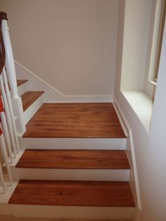 Laminate flooring in a wood pattern against white banisters creates a classic look.