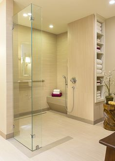 This shower includes many wonderful universal design features that allow for a safe yet luxurious shower experience.  It features a wide, curbless entry which allows a wheelchair user to easily access the space.  Other features include the linear drain, designer handrails, a built-in bench, a hand held showerhear on an adjustable rail, and thermostatic shower controls.  A change in the color of the floor tile functions as a visual cue that there is a glass panel in the area.