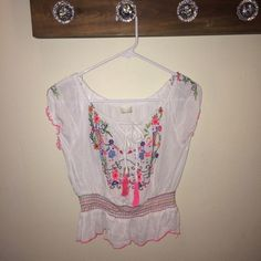 Dainty Crop Peasant Top White peasant crop top. Bright floral designs. Ties and the top. Size tag was removed but fits like an XS. Good condition! Tops Crop Tops