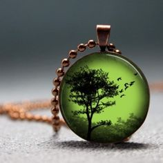 see-through green necklace pendant with black tree silhouette