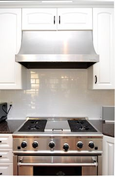 stainless steel oven, range, and hood, white cabinets, dark high gloss countertops... by the BEST custom home builder / remodeler in central Florida   www.allinconstruction.com