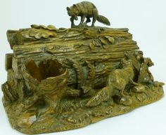 A Stained and Carved Linden Wood Decorative Box and Cover, probably Brienz, Switzerland, circa 1900, modelled as a pile of cut logs around which two foxes play amongst ferns and other plants, 30cm wide, 20cm high - See more at: http://www.tennants.co.uk/Catalogue/Lots/129125.aspx#image
