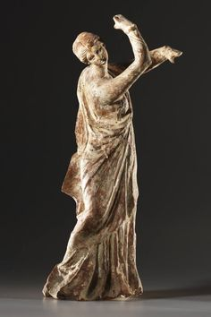 A STATUETTE OF A DANCER From Tanagra, ca. 250 B.C.