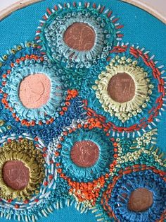 LOVE. coins held onto cloth with beautiful stitches...finally, something to do with my stash of foreign coins.