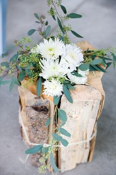 cut flowers in vase disguised by wooden logs.