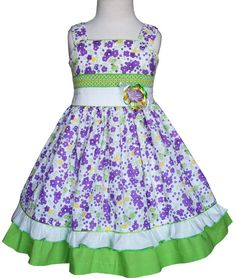 This beautiful violet and green girls summer dress features bands of white and apple green fabric in the waist line and in the hem that contrast the floral design of the fabric, there is a smocking de