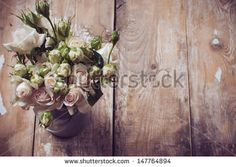 Bouquet of roses in metal pot on the wooden background, vintage style