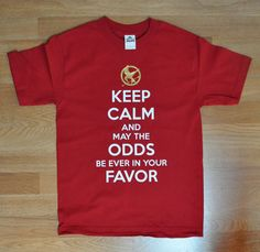 Keep calm and May the odds be ever in your favor Hunger Games Mockingjay Shirt ADULT sizes. $15.95, via Etsy.