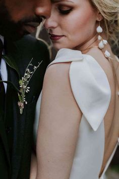 bride looking over her shoulder groom foliage buttonhole at London wedding venue the Charterhouse