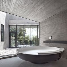 Taking a #bath surrounded by #concrete? Possible in this #unconventional yet absolutely stunning #bathroom with oversize round #tub. #Design by architect k. Find more #unique ideas for your #home and #interior on #homify  #interiordesign #bathroomdesign #bathroomideas #modernbathroom #modernliving #concretebathroom #bathtub #roundtub #freestandingtub #window #glass