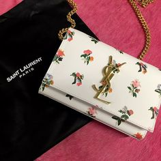 "Saint Laurent Monogram Prairie Flower Small Crossbody Bag, White Multi Details Saint Laurent prairie flower printed calfskin crossbody bag. Curb-chain crossbody strap; 21.3"" drop. Flap top with signature YSL plaque. 4.5""H x 6.7""W x 1.8""D. ""Monogram"" is made in Italy. Designer About Saint Laurent: Founded in 1961, Yves Saint Laurent was the first couture house to introduce the concept of luxury pret-a-porter in a 1966 collection called ""Rive Gauche,"" synonymous with youth and freedom. This…"