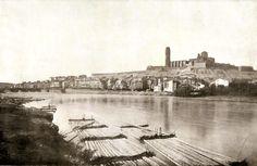 """Encara que avui pugui semblar que el riu Segre s'ha desbordat i estem assistint a una riuada, res de tot això. Aquest era el cabal habitual durant la primavera amb les aportacions de les pluges i el desgel de la neu del Pirineu. Aquests mesos de major cabal s'aprofitaven per baixar fusta pel riu; """"rais"""", o """"tramades"""" com les coneixíem a Lleida, arribaven i formaven """"parades"""" com les de la imatge, esperant a ser desmuntades per a les serradores de la ciutat. (foto: E. Gausí; aprox. 1900)"""