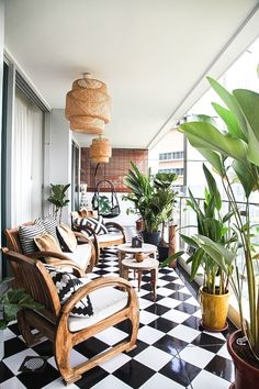 This balcony space is so inviting with the tropical plants, rattan Isle Crawford for Ikea pendants and checked tiled floor which is continued in the geometric cushions.
