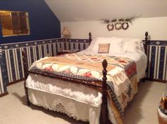 This is the second bedroom upstairs in the farmhouse - the same French country wallpaper is used in this room as well - the antique wooden bed was won at a farm auction years ago ----