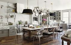 Open cabinets, lighting w/ pot rack, wood floors, & white walls draw us into this stylish kitchen.