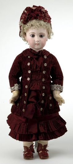 """France, ca 1880, pressed bisque socket head incised 13, blue glass eyes, finely painted brows and lashes, closed mouth, applied pierced ears, original blonde mohair wig with cork pate, marked Jumeau body, wearing original burgundy silk and velvet dress with matching hat, 28"""" t."""