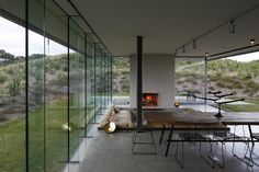 New Zealand, an outdoor fireplace, glass wall to your back and seating for company.