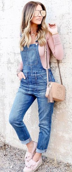#spring #outfits woman in blue denim overall pants and pink long-sleeved shirt learning on wall. Pic by @ashleeknichols