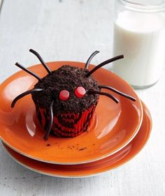 Easy spider cupcakes for Halloween made up of black licorice, crushed cookies, and red gummy candies.