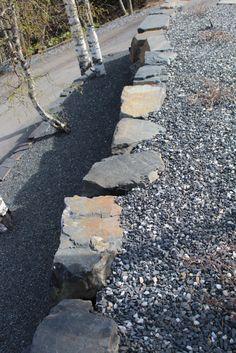 Suurista kivilohkareista tehty tukimuuri louhoksen myyntinäyttelyalueella.