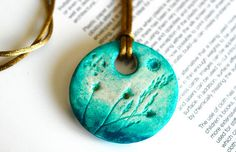 air dry clay necklace, circle shape, wearable art, jewelry, handmade, original painted, floral, aqua green, turquoise, golden bronze. $25.00, via Etsy.