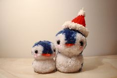 Pom pom pet penguins made with yarn.  I think they look more like bluebirds or swallows.