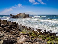 A scene with ocean waves crashing against rocks on the shore. Mountains and clear blue sky in the distance with some wispy clouds.