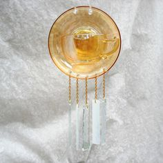 Call it marigold or carnival glass, this OOAK recycled depression glass tea cup and saucer wind chime makes a fabulous addition to your garden or kitchen window!  The Marigold Carnival Glass was produced by the Jeannette Glass Company and became known as Poor Mans Tiffany glass. Often as a prize at carnivals (where it got its name!) it is known for the iridescent quality of the glass. Jeannette produced this Marigold Carnival glass pattern in the 1930s through 1940s -- true Depression Glass…