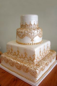 This four tier white and honey gold cake is square on the bottom half and the two top tiers are round. Decorated with gold scoll work and gold buttercream beads. From Blare Solutions www.flickr.com